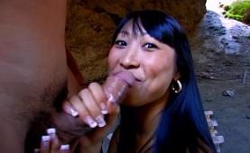 Una puta asiática hace un garganta profunda al aire libre