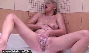 Rubia madura se masturba en la ducha durante un baño de espuma